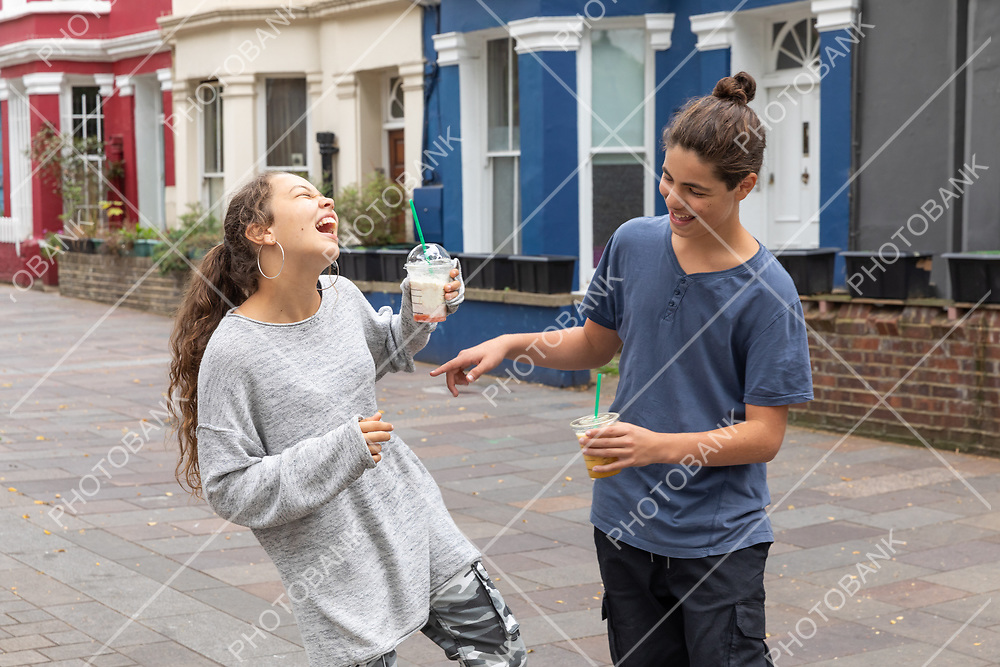 Teenager couple with shake in hand, fun and complicity. Urban context.