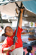 Hmong woman erecting large umbrella at her outdoor cafeteria. Hmong Sports Festival McMurray Field St Paul Minnesota USA