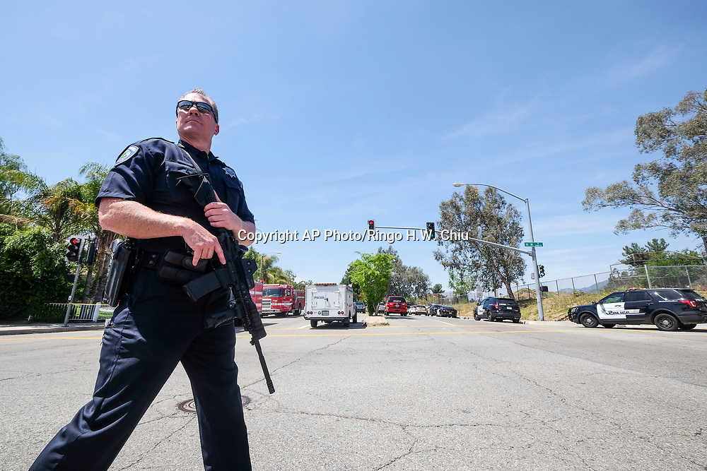 A police office stands guard outside the North Park School after a shooting ,Monday, April 10, 2017, in San Bernardino, Calif.. An apparent murder-suicide inside an elementary school classroom in San Bernardino left two adults dead, including a teacher, and two students wounded, police and school officials said. (AP Photo/Ringo H.W. Chiu)