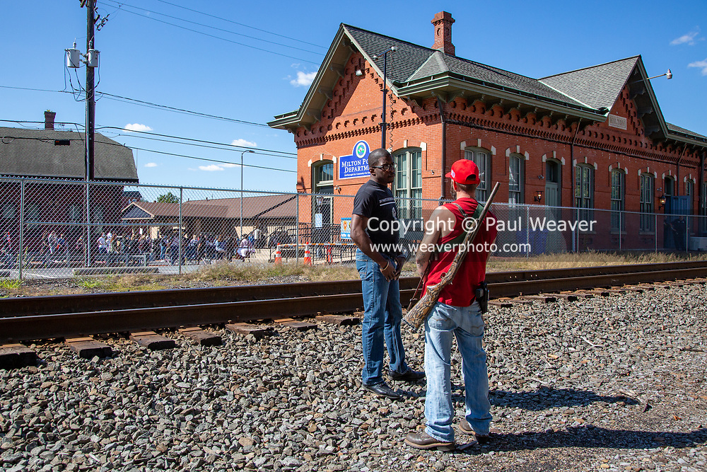 An armed counter-protester wearing a red Make America Great Again hat and a Black Lives Matter protester speak as a BLM rally is going on in Milton, Pennsylvania on September 20, 2020.