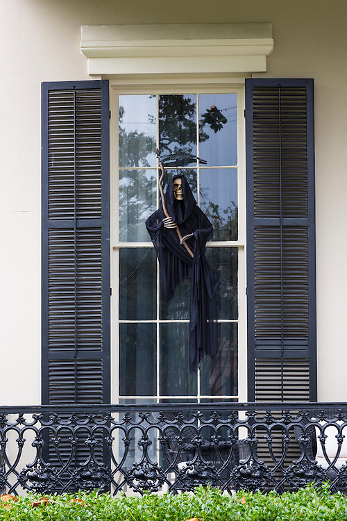 Scary Halloween voodoo grim reaper ghost character at mansion house with wrought iron in the Garden District of New Orleans, USA