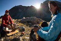 A young couple prepares a meal while camping in Grand Teton National Park, Jackson Hole, Wyoming.