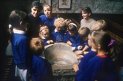 Group of junior school children standing around font in church listening to vicar talking,