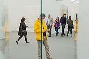 "New York, NY - 6 May 2016. Frieze New York art fair. A man in a yellow jacket seen reflected in Idris Khan's ""Overture, a construction of 7 glass sheets, in the Sean Kelly gallery."