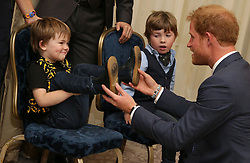 Prince Harry (right) reacts as he greets Noah and Oscar, the children of WellChild Special Recognition Award Winner Jill Evans, (unseen), as he attends the WellChild Awards in London. The awards recognise the courage of seriously ill children, their families and carers.