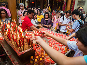 """31 JANUARY 2016 - BANGKOK, THAILAND: People make merit at Wat Mangon Kamlawat, the largest Mahayana (Chinese) Buddhist temple in Bangkok, before the celebration of Chinese New Year. Thailand has the largest overseas Chinese population in the world; about 14 percent of Thais are of Chinese ancestry and some Chinese holidays, especially Chinese New Year, are widely celebrated in Thailand. Chinese New Year, also called Lunar New Year or Tet (in Vietnamese communities) starts Monday February 8. The coming year will be the """"Year of the Monkey.""""           PHOTO BY JACK KURTZ"""