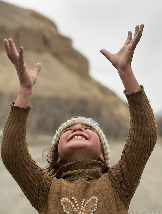 Girl looking up with stretched arm. In Shimshal, one of the remotest village in the Karakoram mountains, and the highest settlement in the Hunza and Gojal region.