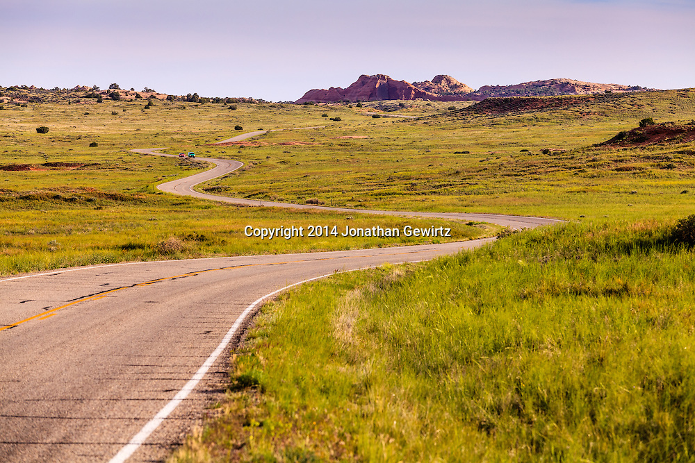 A paved road winds through high desert meadows of Canyonlands National Park, Utah. WATERMARKS WILL NOT APPEAR ON PRINTS OR LICENSED IMAGES.<br /> <br /> Licensing: https://tandemstock.com/assets/76915669