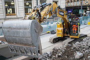 Workman operating a digger lifts large quantities of rubble into a truck at the construction site for work on the update to the Midland Metro tram public transport system in the city centre along Corporation Street on 3rd August 2021 in Birmingham, United Kingdom. The original tracks are being pulled up and relaid, while a new line is also under construction and due to open later in the year. The Midland Metro is a light-rail tram line in the county of West Midlands, England, operating between the cities of Birmingham and Wolverhampton via the towns of West Bromwich and Wednesbury. The line operates on streets in urban areas, and reopened conventional rail tracks that link the towns and cities. The owners are Transport for West Midlands with operation by National Express Midland Metro, a subsidiary of National Express. TfWM itself will operate the service from October 2018.