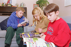 Group of young children sitting in living room reading magazines and playing gameboy,