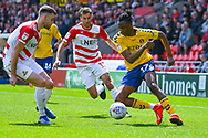 Joe Aribo of Charlton Athletic (17) and Ben Whiteman of Doncaster Rovers (8) with Matty Blair of Doncaster Rovers (17) in action during the EFL Sky Bet League 1 play off first leg match between Doncaster Rovers and Charlton Athletic at the Keepmoat Stadium, Doncaster, England on 12 May 2019.