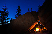 Marco Binotti (left) and David Coffey draw cave paintings by firelight in their cave camp in McMurdy Park, Lost Creek Wilderness, Colorado.