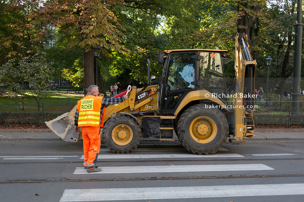 A road construction worker stops traffic as a tractor drives in front of cars on a street in central Krakow, on 23rd September 2019, in Krakow, Malopolska, Poland.