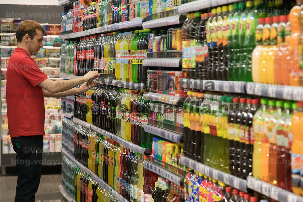 Salesman adjusts soft drink products on the selves before the official opening ceremony of a new Spar food shop in downtown Budapest, Hungary on Aug. 22, 2018. ATTILA VOLGYI