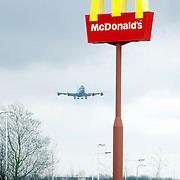 Vliegtuig, KLM Boeing 747 landend op Schiphol, paal met McDonalds logo.reclame, lichten, landingslichten