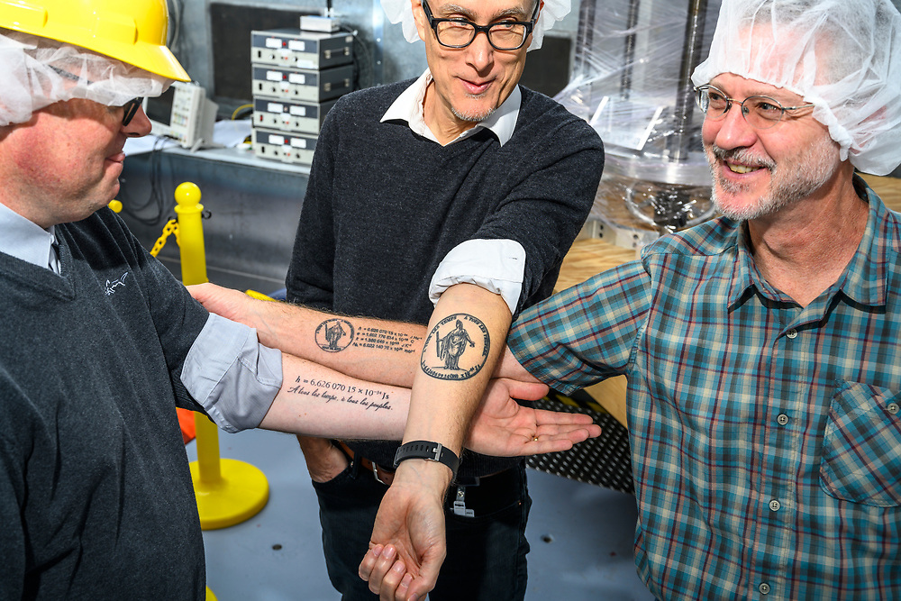 """Gaithersburg, Maryland - November 09, 2018: NIST-4 Kibble Balance lead scientists (L-R) Dr. Stephan Schlamminger, Dr. Jon Pratt, and Dr. David Newell, all got super-nerdy science tattoos. The one factor all their tattoos have in common is the Plank Constant, """"h = 6.626070150 × 10-34 kg⋅m2/s"""" which will be the new standard for which the kilogram is measured.<br /> <br /> Scientists at the National Institute of Standards and Technology have helped improved methods for definitively measuring a kilogram. Representatives from 57 countries will vote at the General Conference on Weights and Measures in Versailles, France to redefine four basic units of measurement November 16, 2018. <br /> <br /> CREDIT: Matt Roth for The New York Times<br /> Assignment ID:  30226894A"""