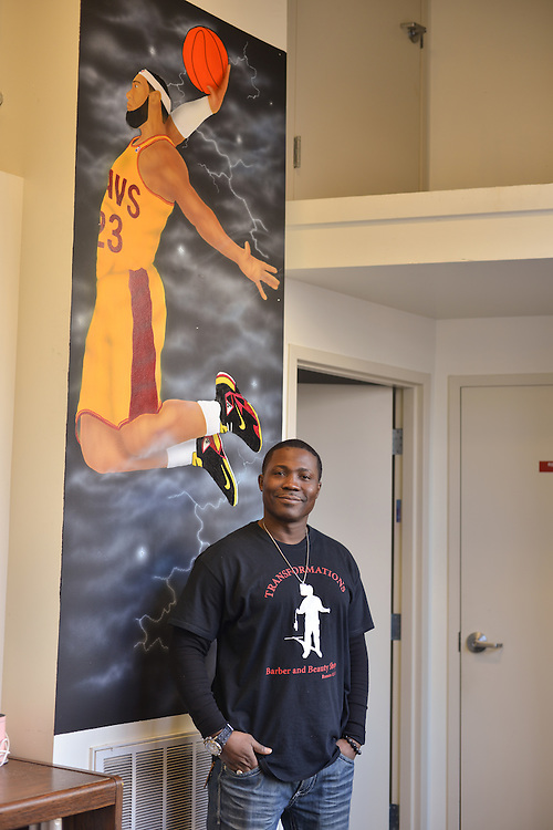 Owner of Transformations Barber and Beauty Salon standing next to a wall mural of LeBron James.