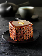A modern designed cake with a sponge case and chocolate filling in a Traditionl black Japanese tea setting