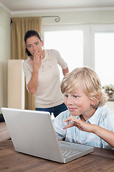 Shocked woman watching her son using laptop in living room, Bavaria, Germany