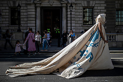 © Licensed to London News Pictures. 20/09/2019. London, UK. A performer wearing 'Dress for Our Time', a piece by artist and designer Helen Storey made from a UNHCR tent, walks down Whitehall in London as tens of thousands join the Global Climate Strike in London. Protests about the climate crisis are being led by young people in cities around the world, with millions expected to attend. Photo credit: Rob Pinney/LNP