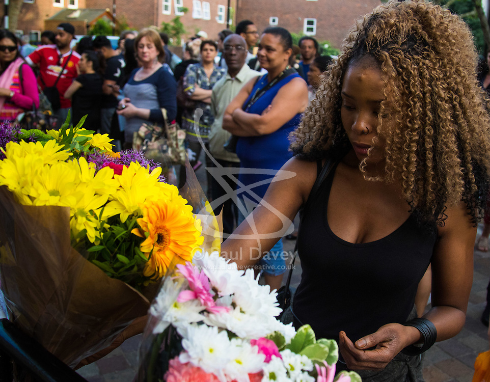 London, June 15th 2017. Local residents and well-wishers gather at a short vigil outside Notting Hill Methodist Church near the scene of the Grenfell Tower Fire Disaster in which so far seventeen people have been reported killed, with dozens injured, many still missing and scores of people rendered homeless. PICTURED: A young woman adds her flowers to the growing collection.