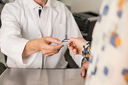 Patient giving a health insurance card to doctor, Munich, Bavaria, Germany