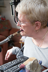 Woman with Cerebral Palsy using mouth piece of Possum equipment to control her personal environment,