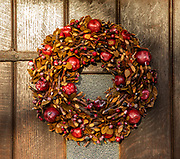 Christmas wreath on house door made of twigs, dried leaves, and apples, UK