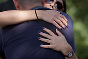 A woman with blue painted nails holds on tight to her partner in a public street. The amourous couple squeeze each other, hugging in a gesture of fond farewell or a happy hello. Either way, we see the lady's hands spread across the back of her friend or partner, comforted and comfortable - or in a desperate bid not to let go. Their relationship is close and intimate, their support of each other, proof of their dependency.