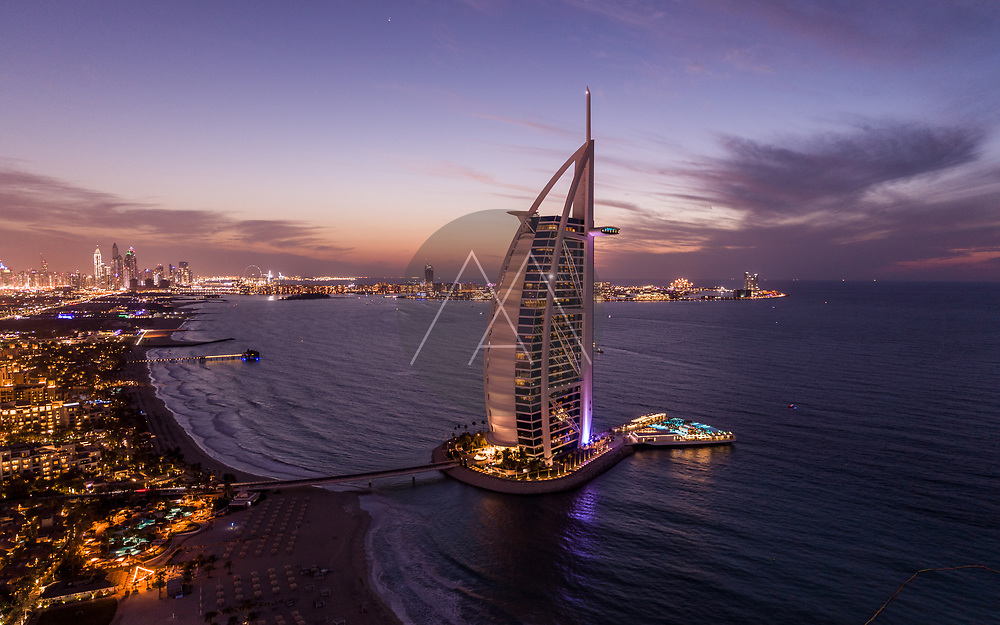 Aerial view of Burj Al Arab luxury hotel at sunset with cityscape facing the Persian gulf sea in background, Dubai, United Arab Emirates.