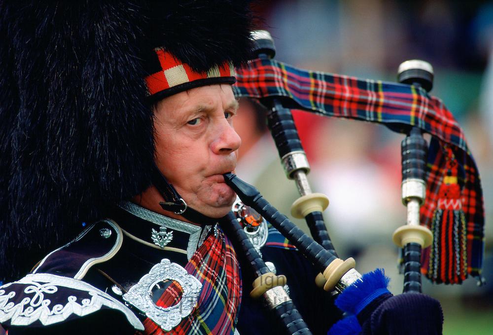 Scottish Piper playing bagpipes at the Braemar Games, Braemar, Scotland