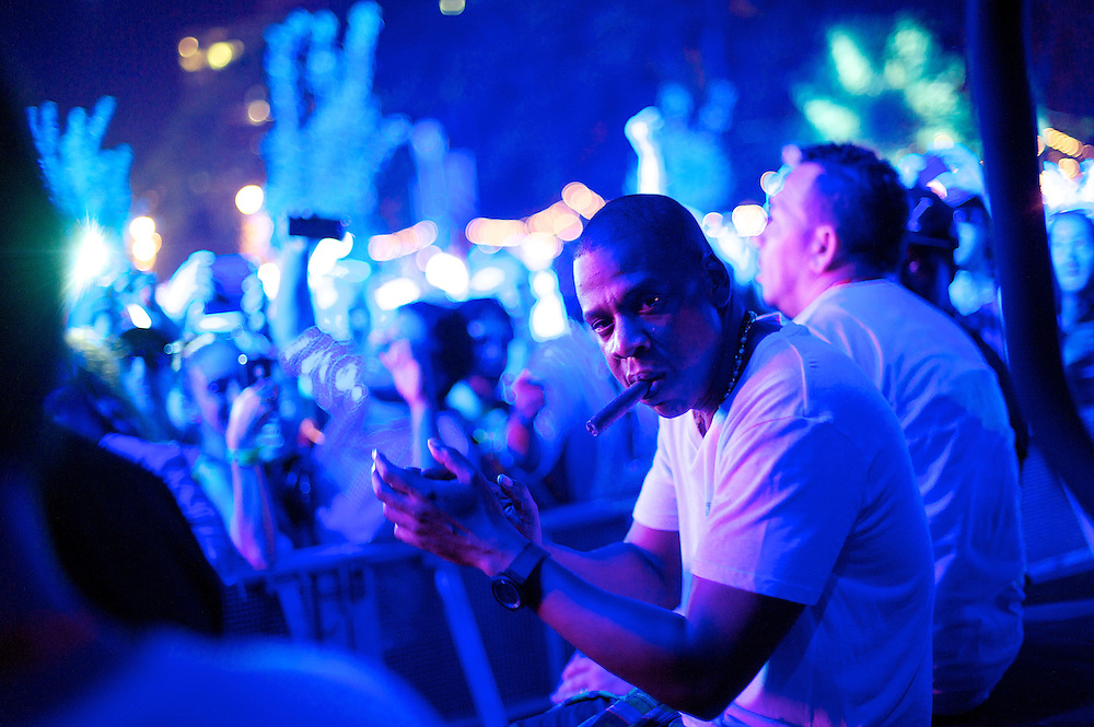 Jay-Z smokes a cigar listening to DeadMau5 perform at the Budweiser Made in America Music Festival in Philadelphia, PA.