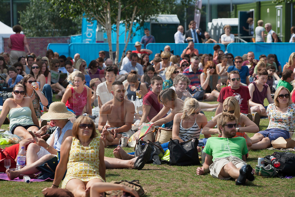 © licensed to London News Pictures. London, UK 10/08/2012. People sunbathing and watching the Games in Potters Fields Park on 10/08/12. Photo credit: Tolga Akmen/LNP