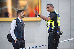 A police officer speaks to a member of the public as police cordon off the area around at the scene in London Bridge and Borough Market in London following last night's terrorists incidents.