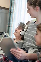 Senior woman listing music with grand children in rest home
