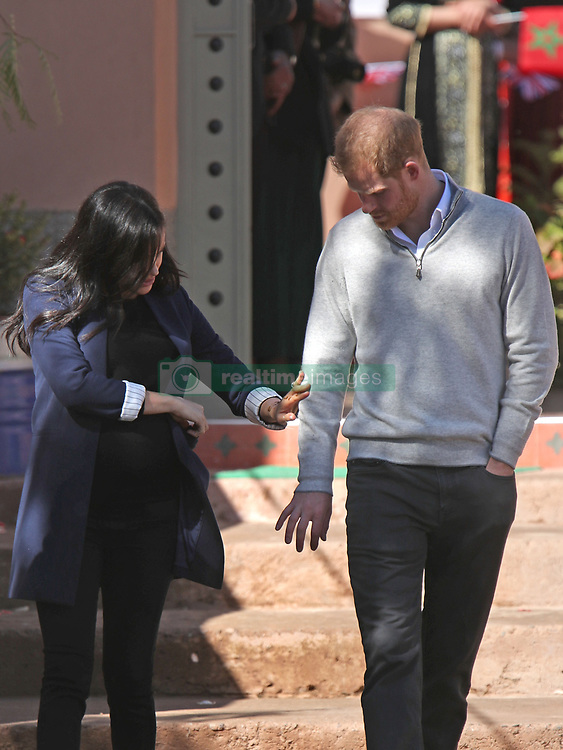 Duchess of Sussex brushes some dust off the arm of the Duke of Sussex as they arrive to invest Michael McHugo, the founder of 'Education for All', with an MBE during their visit to the original 'Education For All' boarding house in Asni Town, Atlas Mountains on the second day of their tour of Morocco.
