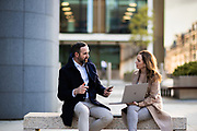 Business man and woman working outside with a laptop and talking, whilst sat on a bench in front of corporate office buildings on the Esplanade, St Helier, Jersey, CI