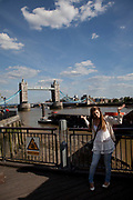 Tourist poses for a photo with Tower Bridge in the background. This iconic bridge across the River Thames is hugely popular with tourists.