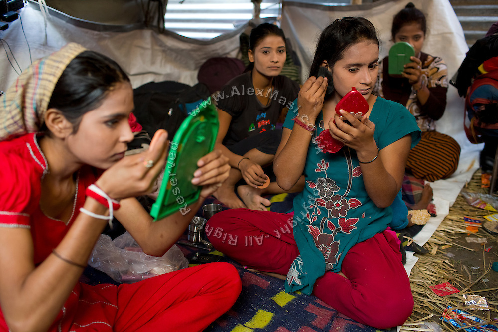Young women are applying makeup before performing at one of the regular night dance shows being set up during the yearly Sonepur Mela, Asia's largest cattle market, in Bihar, India.