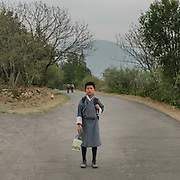 A boy on his way to school with his lunch box. Punakha, Bhutan