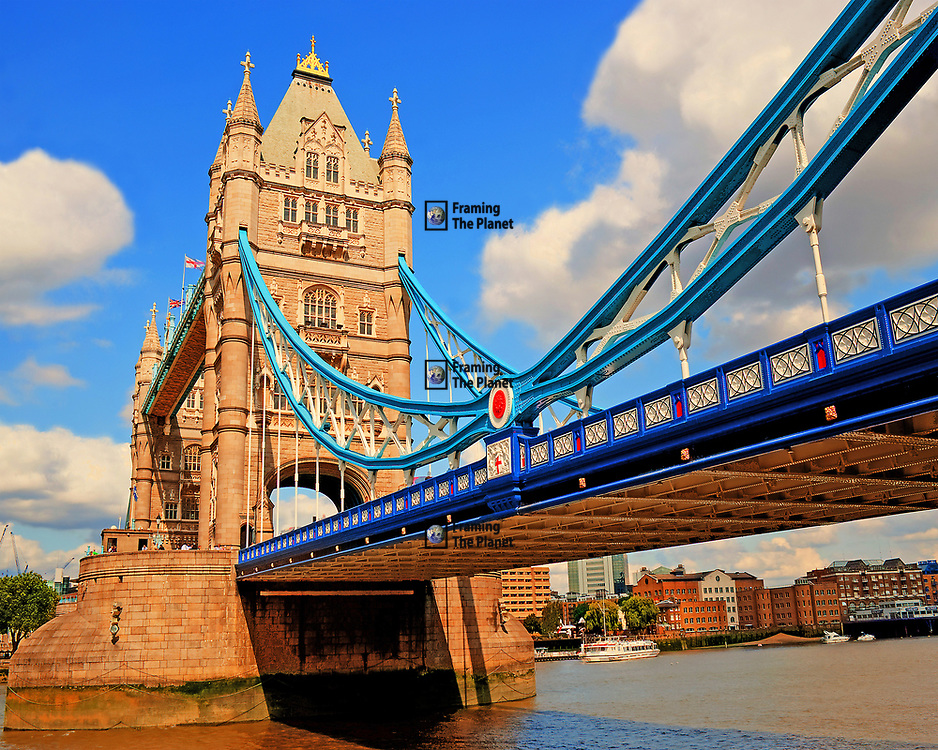 This image of one of the most recognisable landmarks in London, the historic Tower bridge. I was very lucky to have a nice bright day to get the perfect light to capture this fantastic bridge so well. Sometimes confused by tourists as London Bridge, this landmark is one of the most easily recognisable in the city. <br /> <br /> This photo was taken from the south bank and shows us the size of this Victorian structure from close up. We have a nice blue sky with the water running in the river framing the monument. Up close we can see the steel structure of the bridge and the towers that contain the engines to raise the bridge to let tall ships pass up river and into the port of London once the centre of the British Empire and now the capitol of the United Kingdom.