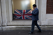 In the year that Britain will start the process of Brexit leaving the European Union, an Asian businessman walks past a crumpled British Union Jack flag in the window of a City retailer, on 2nd February 2017, in the City of London, England.