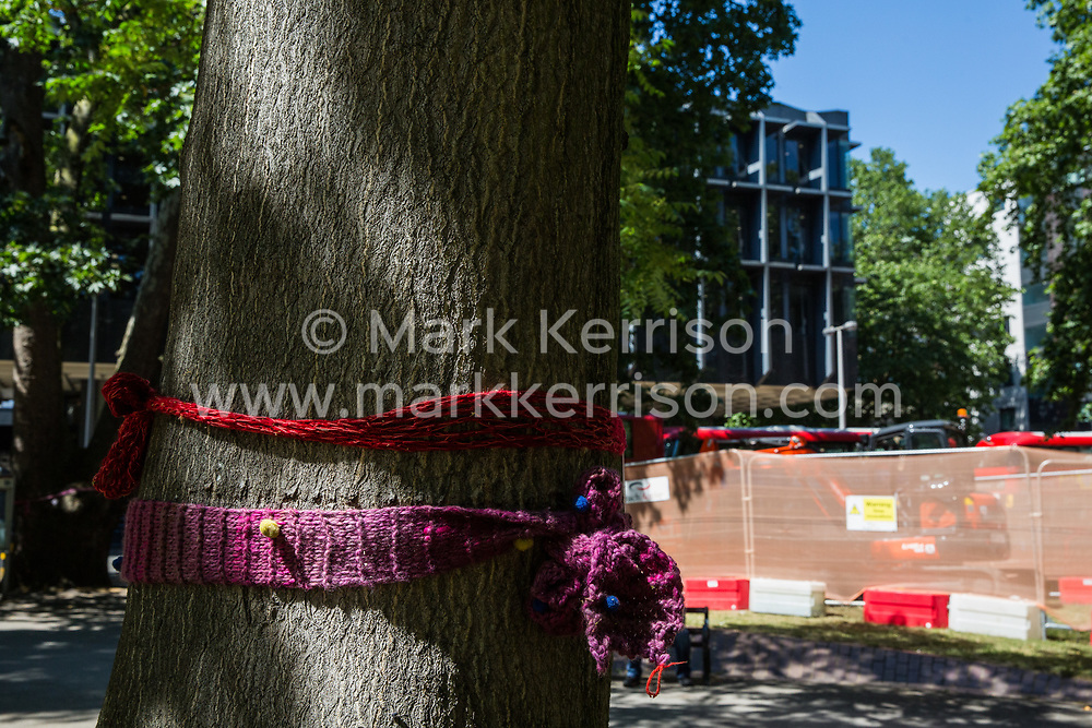 London, UK. 26th June 2018. Works continue in Euston Square Gardens involving the planned felling by HS2 Ltd of mature London Plane, Red Oak, Common Lime, Common Whitebeam and Wild Service trees to make way for temporary sites for construction vehicles and a displaced taxi rank as part of preparations for the HS2 high-speed rail line. Local residents and campaigners have attached knitted bands to the trees in protest against their planned felling.