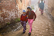 Jasbir Kaur takes her younger brother to school before heading onto her own one early on a misty winter  morning, Chita Kalaan village, Punjab, India