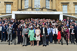 The Duke and Duchess of Sussex (front centre right) Stand with the Prince of Wales and the Duchess of Cornwall (front centre left) and guests during a garden party at Buckingham Palace in London, which they are attending as their first royal engagement as a married couple.