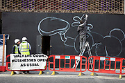 Graffiti artist begins on a new piece on a hoarding in Soho in London, United Kingdom. Street art is an ever changing visual enigma, as the artworks constantly change, as councils clean some walls or new works go up in place of others. While some consider this vandalism or graffiti, these artworks are very popular among local people and visitors alike, as a sense of poignancy remains in the work, many of which have subtle messages.