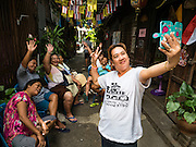 "15 AUGUST 2016 - BANGKOK, THAILAND:  Women who live in the Pom Mahakan slum pose for a ""selfie"" after they were given eviction notices Monday. Final eviction notices were posted today and residents of the slum have been told they must leave the fort by September 3, 2016. The Pom Mahakan community is known for fireworks, fighting cocks and bird cages. Mahakan Fort was built in 1783 during the reign of Siamese King Rama I. It was one of 14 fortresses designed to protect Bangkok from foreign invaders. Only two of the forts are still standing, the others have been torn down. A community developed in the fort when people started building houses and moving into it during the reign of King Rama V (1868-1910). The land was expropriated by Bangkok city government in 1992, but the people living in the fort refused to move. In 2004 courts ruled against the residents and said the city could take the land.      PHOTO BY JACK KURTZ"