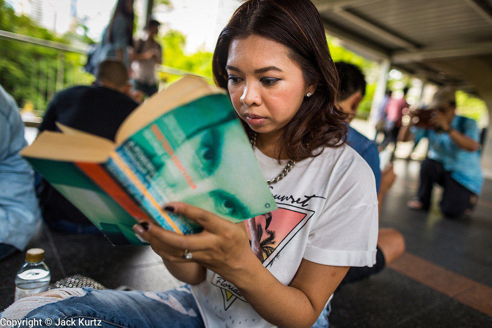 """31 MAY 2014 - BANGKOK, THAILAND: A woman sits in the Skywalk between the BTS Skytrain Siam and Chit Lom stations to silently read George Orwell's """"1984"""" and other books about civil disobedience and nonviolent protest. The protests are based on the """"Standing Man"""" protests that started in Turkey last summer. Authorities made no effort to stop the protest or interfere with the people who were reading. Bangkok was mostly quiet Saturday. There were only a few isolated protests against the coup and military government.    PHOTO BY JACK KURTZ"""