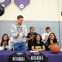 Miyamura Lady Patriot Odessa Begay's teammate, coach, and family clap after she signs a letter of intent to attend Haskell Indian Nations University and play for the Fightin' Indians women's basketball team Friday, April 12 at Miyamura High School. Her teammate Fetisha Johnson, far left, signed with Haskell in February.