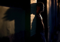 portrait of cuban man during golden hour against brick wall